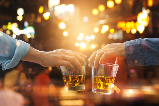 Cheers clinking of friends with bourbon whiskey drinks in party night after work on colorful background