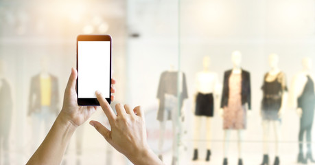 Hands using mobile smart phone and take a photo of display clothing store,  shopping online concept
