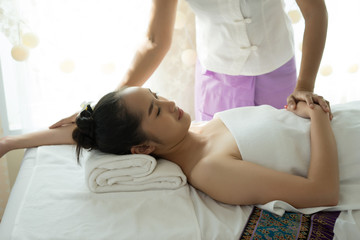 Young beautiful woman receiving body massage in spa.