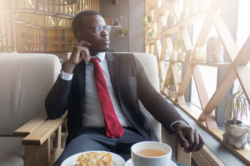 Indoor portrait of young African American businessman in cozy cafe during lunchtime, drinking coffee and having meal, looking through window thinking about future plans or current tasks at work