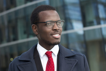 Outdoor headshot of young handsome African businessman pictured in urban environment dressed formally in suit, shirt, tie and coat, looking through eyeglasses to street with optimistic smile