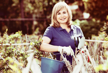 Smiling woman  holding horticultural tools in garden on sunny day