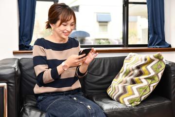 スマートフォンを操作する若く美しい日本人女性
