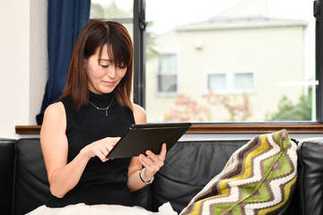 リビングのソファでタブレットを操作する日本の女性