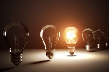 A row of light bulbs. One is glowing. 3D rendered illustration.