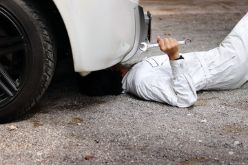Professional mechanic in white uniform lying down and fixing under car. Auto repair service.
