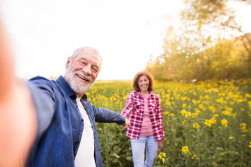 Senior couple with smartphone outside in spring nature.