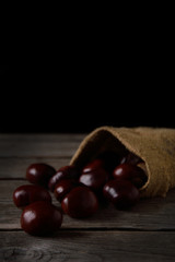 Chestnuts strewing from a bag on a wooden background in dark tones with a leaf with a very high color