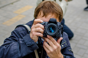 Male photographer taking picture looking at the camera