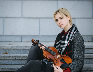 Beautiful girl in coat holding a old violin.