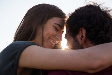 Happy woman embracing with man and posing in back light on nature.