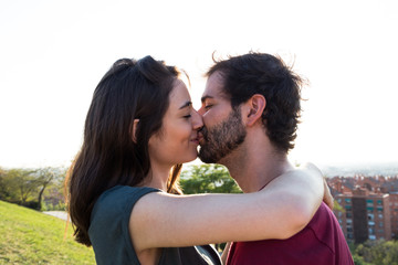 Side view of casual young couple kissing gently on background of green lawn in sunlight.