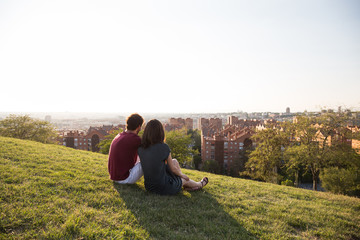 Back view of loving people posing on green meadow with view of city in sunlight.