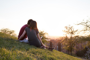 Back view of young couple sitting on green meadow with smartphone on background of city in sunlight.