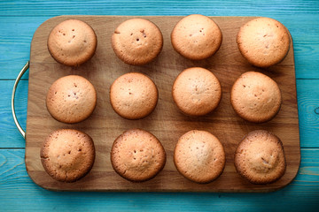Fresh muffins on a cutting board on a wooden blue background. Background.