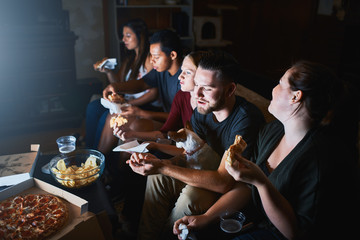group of friends watching tv at night and eating pizza together