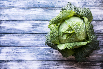Raw savoy cabbage on wooden background. Organic food