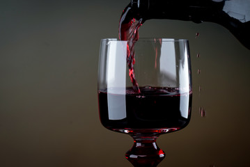 Pouring red wine into the glass against rustic background