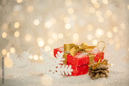 red holiday christmas present gift on snow with sparkling bokeh lights in the background