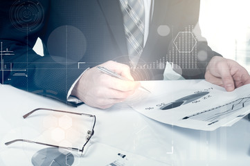 business documents on office table with laptop computer and graph financial digital diagram and businessman working in the background