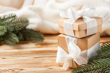 Craft gift boxes with white ribbon, bow, green Christmas tree, decorations, white plaid on wooden background. Xmas and New Year congratulation card, banner, flyer.