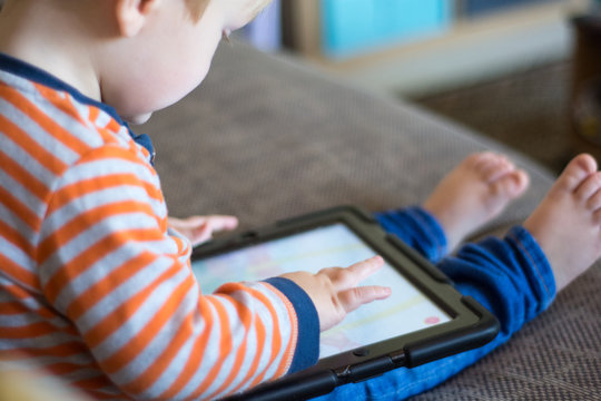 Child using a touch screen tablet to play learning game