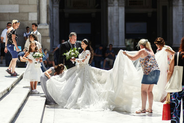 Women help bride to walk upstairs to the church