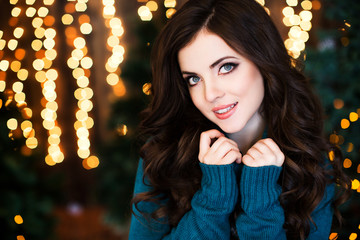 Beautiful smiling woman with wavy hair on a blurred Christmas background.