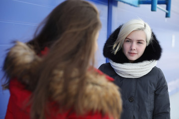 Young beautiful girl on a walk in winter at blue wall