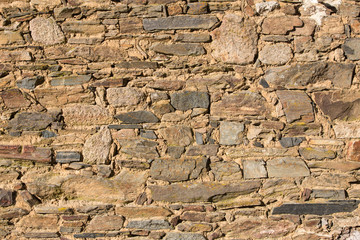 Side view of the sunlit stone patterns on an old dry stone wall.