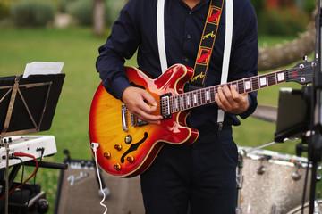Man plays a guitar standing in the garden