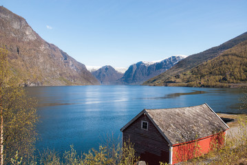 Fjord with mountains as backdrop with roof of small hut in foreground