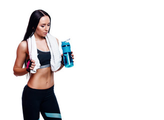 Fitness girl with shaker and towel on a white background. Attractive athletic woman relaxing after workout.