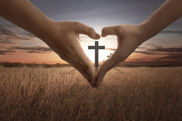 People hand making heart sign with bright cross inside