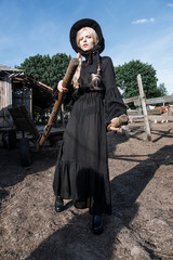 Fashion young woman wearing stylish black dress and hat at countryside. Amish fashion style.