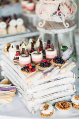 Baked baskets with berries stand among other delicious desserts on the table