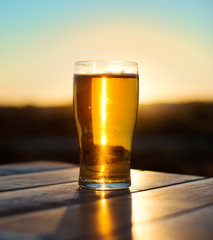 Glass of beer on the sunset.