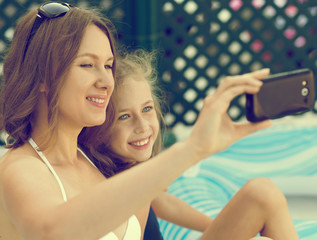 Mother and daughter taking selfie on vacations.
