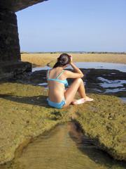 Niña sentada sobre una roca en la playa.