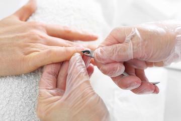Wycinanie skórek przy paznokciach. Dłonie kobiety podczas zabiegu manicure