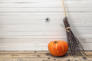 Halloween pumpkin and witch's broom on a wooden background. Halloween background.