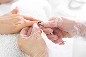Wycinanie skórek cążkami. Dłonie kobiety podczas zabiegu manicure