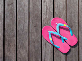 Pink flip flop on wooden floor