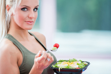 healthy young woman eating salad at gym