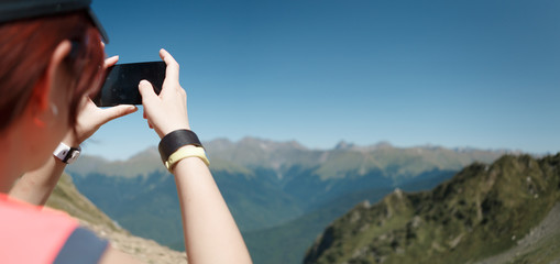 Photo of tourist woman photographing mountain