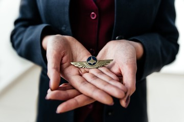 Stewardess closeup holds in his hands the icon of aviation