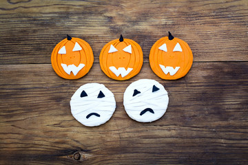 Pumpkins and mummies on wooden background