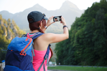 Image from back of tourist woman photographing mountain
