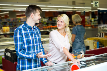 Happy family standing near display with frozen food