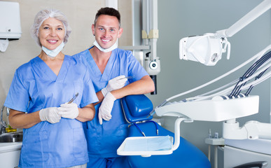 Two professional confident dentists near dental chair